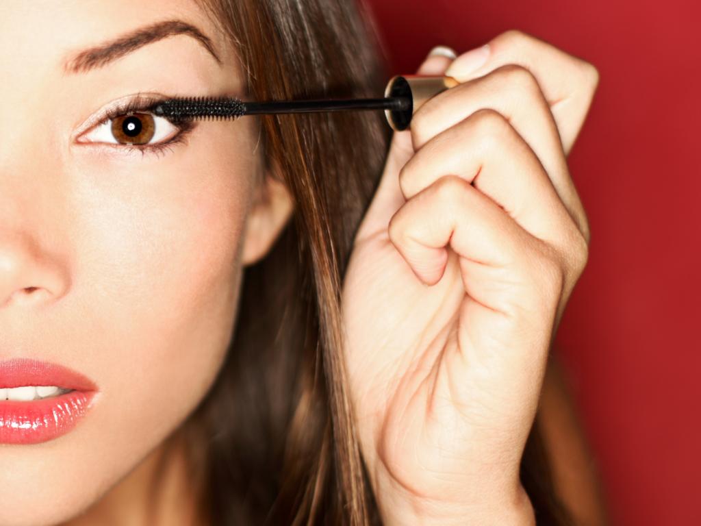 Woman putting mascara makeup on