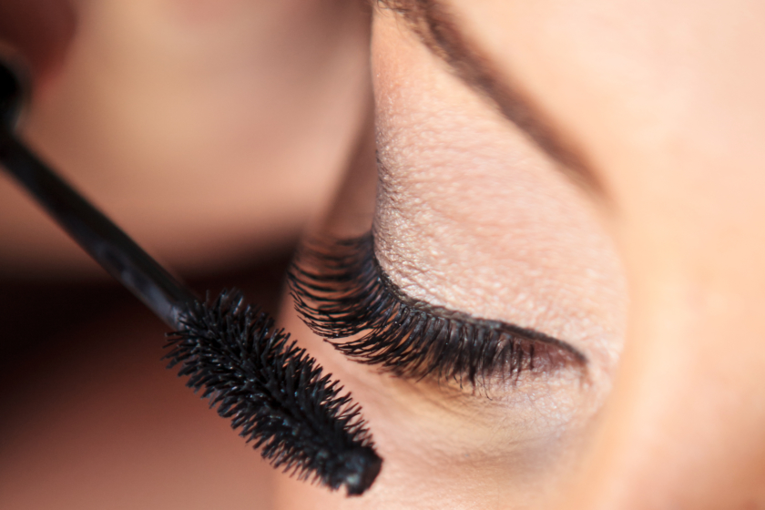 A woman applying mascara