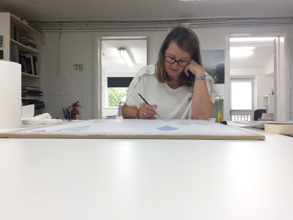 Wallpaper designer Elizabeth Ockford painting a wallpaper design