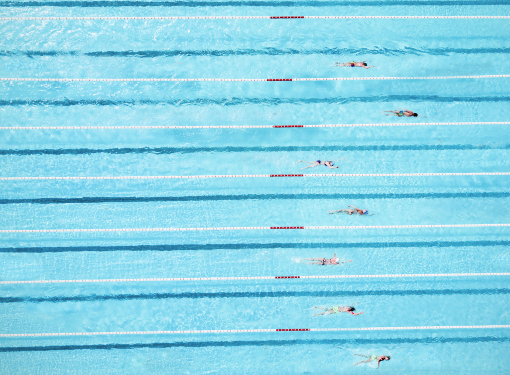 Benefits of swimming: Aerial view of swimmers in Olympic pool