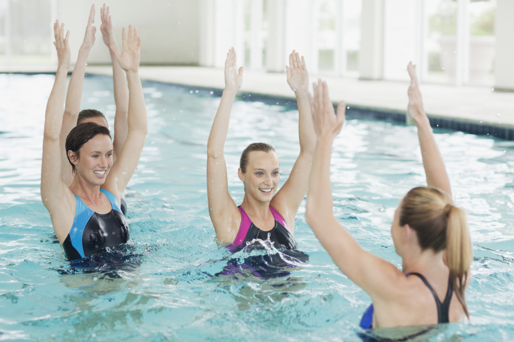 Benefits of swimming: Women taking water aerobics class in swimming pool