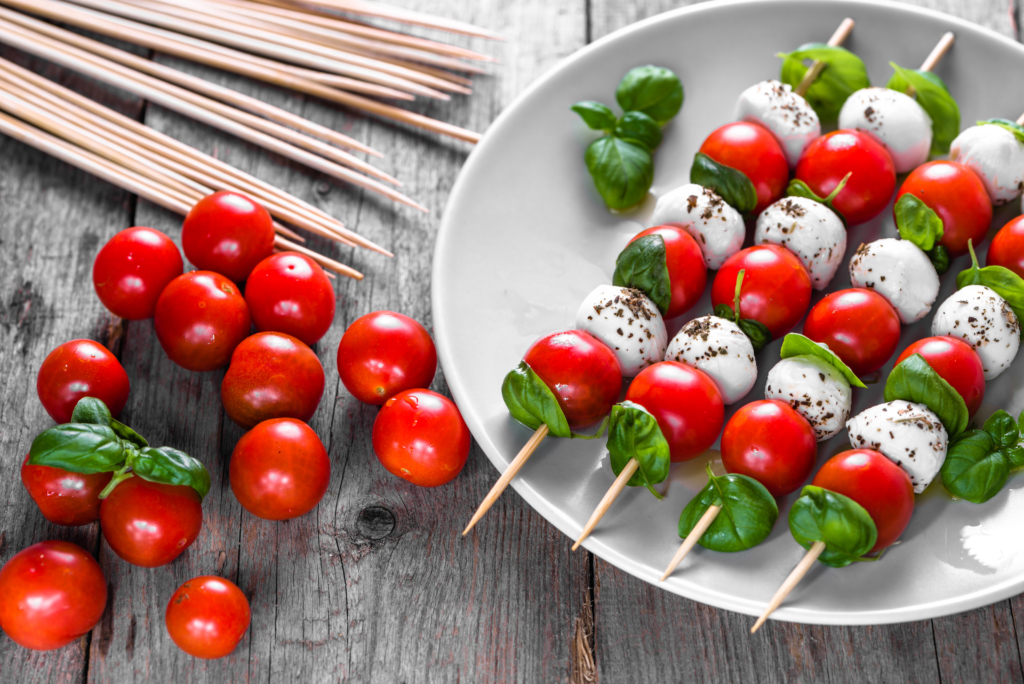 hristmas canapés Caprese salad - skewer with tomato, mozzarella and basil, italian food and healthy vegetarian diet concept