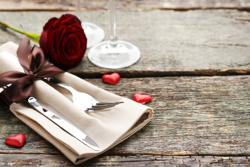 romantic dinner Kitchen cutlery with napkin and red rose on wooden table