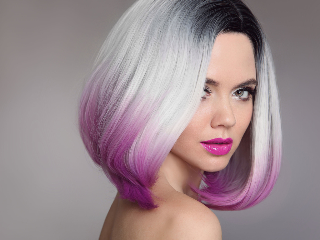 hairdresser Coloured Ombre hair extensions. Beauty Model Girl blonde with short bob purple hairstyle isolated on gray background. Closeup woman portrait.