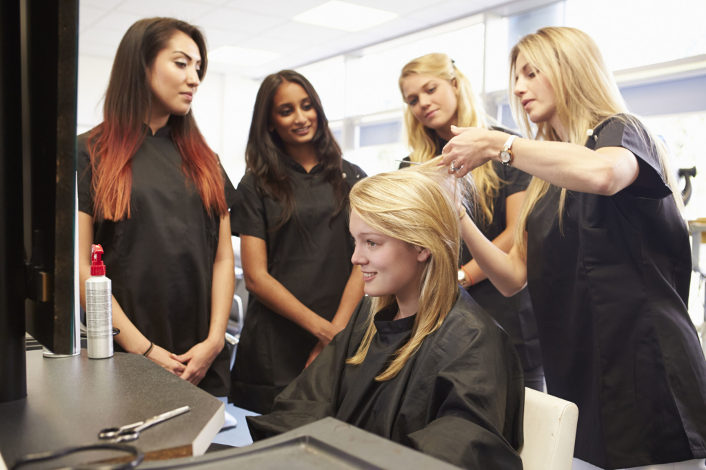 hairdresser Teacher Helping Students Training To Become Hairdressers