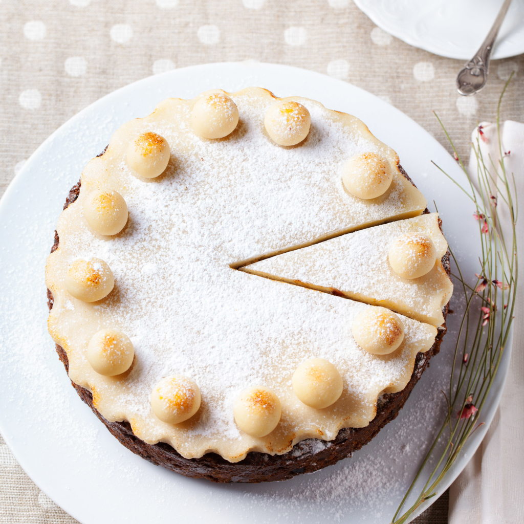 Easter recipes Traditional English Easter cake with marzipan decoration on white plate.