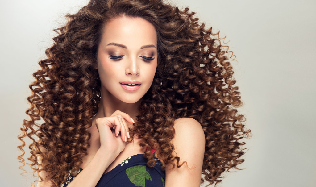 hairdresser dry hair tips Soft smile on the face of flawless young girl. Brown haired woman with voluminous, shiny and curly hairstyle.