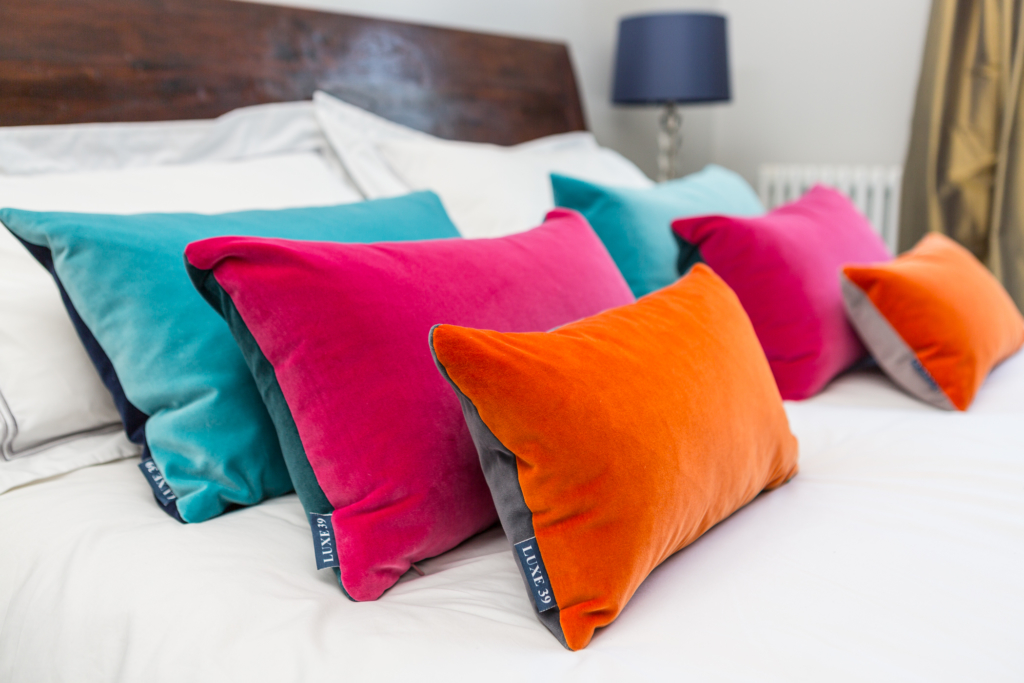 velvet cushions on a bed in bold brights
