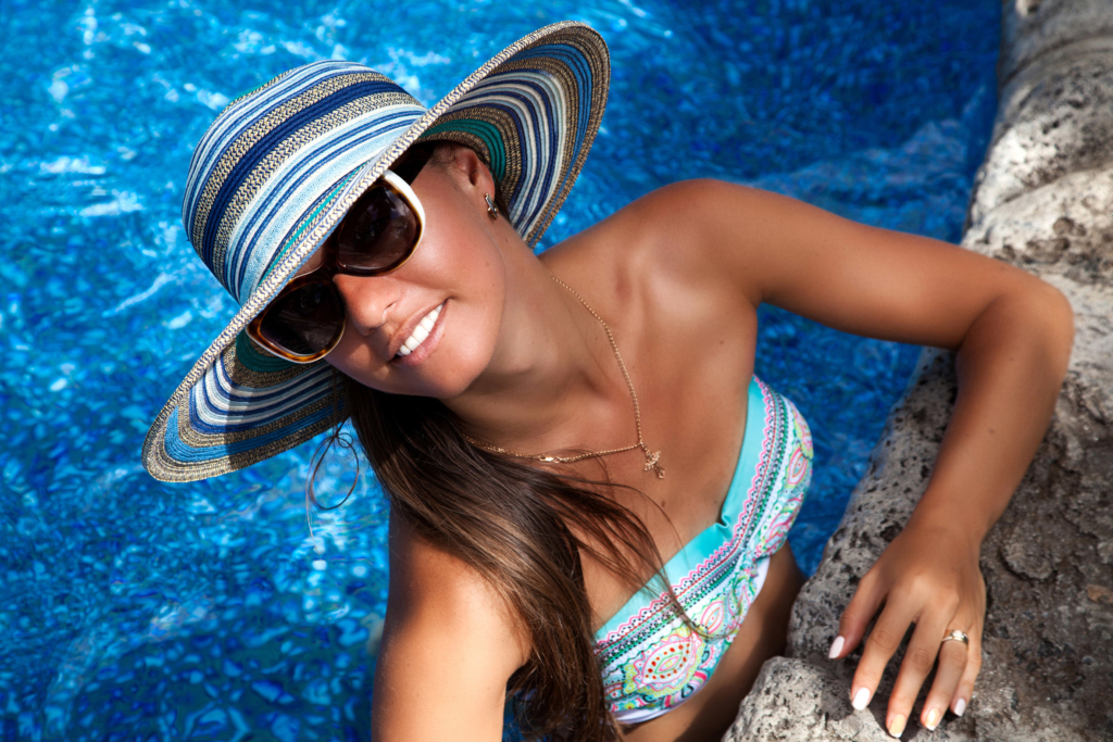 fake tan woman wearing shades and sun hat in pool