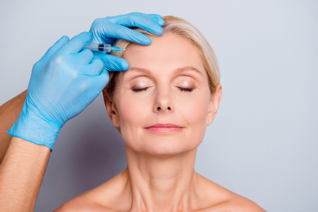 local dentist Portrait of calm serious aged woman with wrinkle keeping eyes close getting injection in forehead in professional clinic isolated on grey background