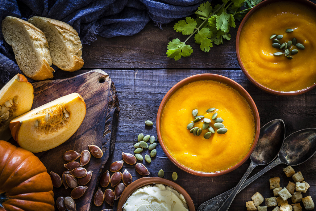 autumn recipe ideas Pumpkin soup with ingredients on rustic wooden table