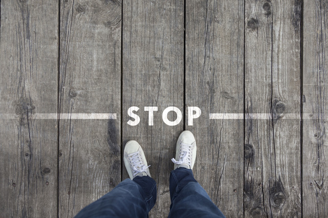 How to combat stress is to stop and say no - Man standing on the wooden boards with stop message on the floor, point of view perspective used.