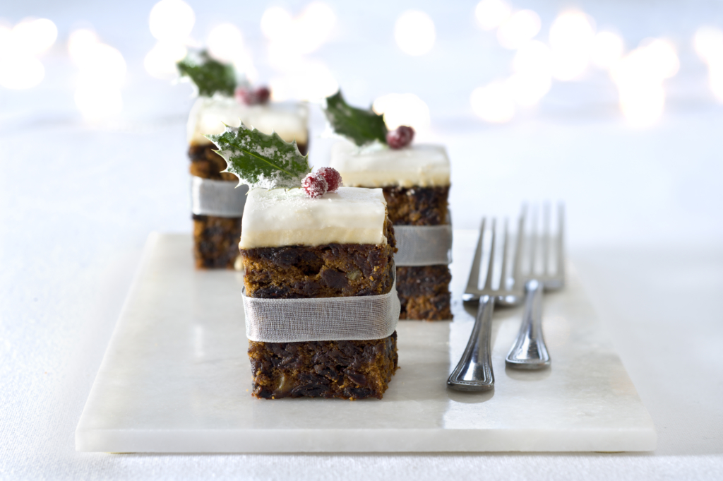 Christmas dessert squares of Christmas cake adorned with a cranberry