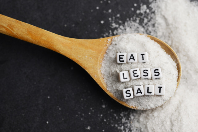 Eat less salt advice written with plastic letter beads on granulated salt for a balanced diet