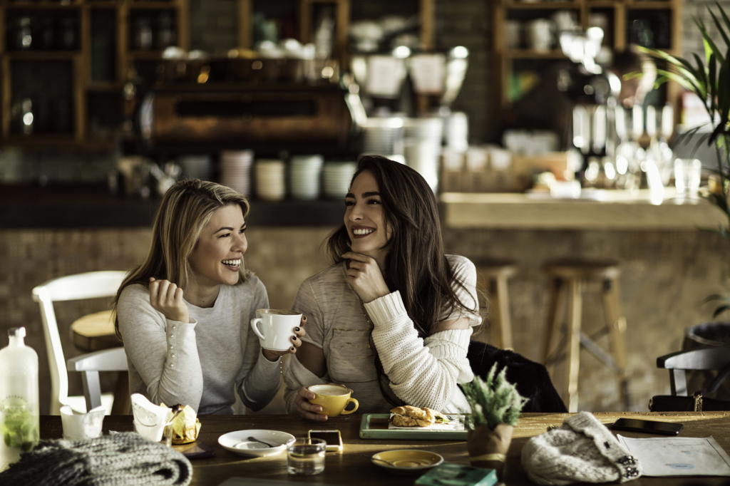 Two cheerful women having fun during coffee time in a cafe