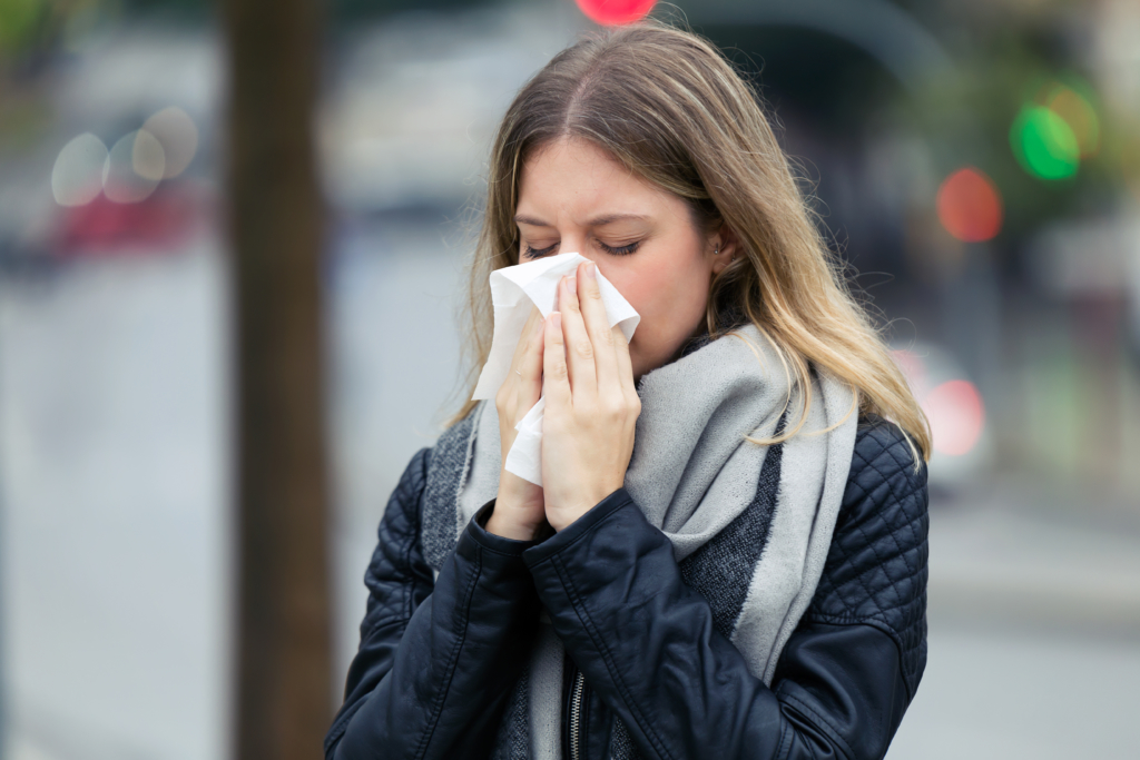 immune system booster guide Illness young woman sneezing in a tissue in the street.